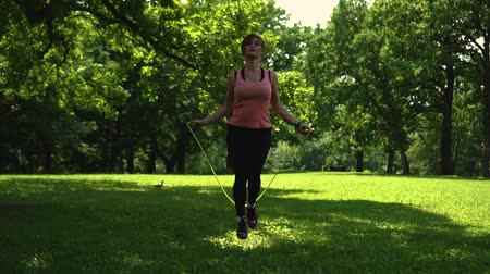 girl jumping rope in the park on the grass Stok Video