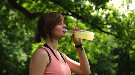 girl athlete drinks water in the park Stok Video