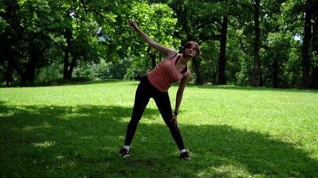 girl doing fitness in the park on the grass