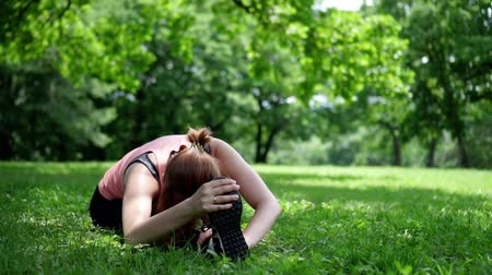 girl doing stretching on the grass in the park