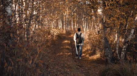 the guy is walking in the autumn forest Stok Video