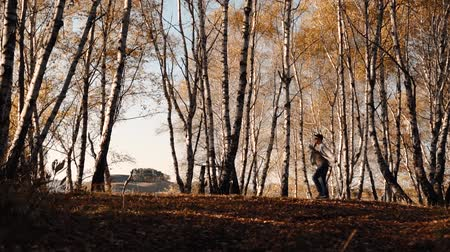 guy jumping fun in the autumn forest