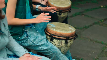 areca : Young white girl playing Bongo drum with friends close up