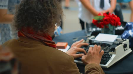 photojournalist : Vintage journalists desk style, he is working and typing on his typewriter at public cafe