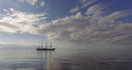 海賊 : Big Sailing Ship In The Calm Mirror-Smooth Sea On The Background Of The Mountain Coast. The Four-mast Ship Drifts With Lowered Sails On Sunset. 動画素材