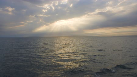 Beautiful Rays of the Sun Fall On The Surface Of The Sea Through Clouds. View from the Floating Yacht
