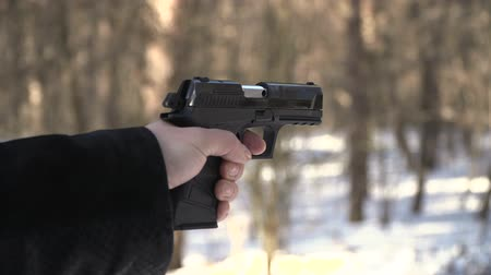 bulletproof : gun shot in slow motion. winter landscape man hand Stock Footage