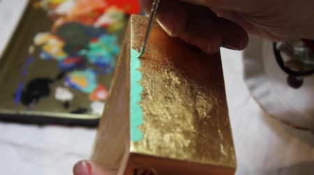 restorer : Artist painting decorative details with a brush to a golden box