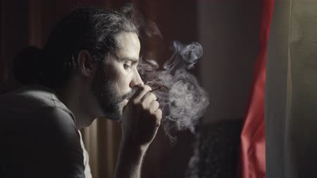 depressant : Portrait of a man smoking in a room next to the window