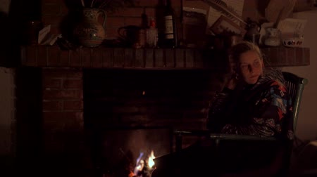 fireside : Portrait of a young woman in a fireplace Stock Footage