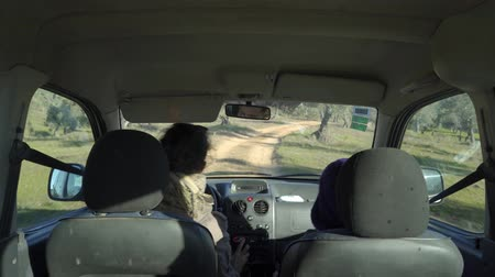 mirror glass : Couple in the interior of a car driving down a dirt road through the countryside