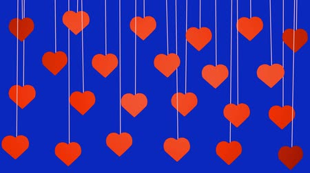 Animated red hearts shapes hanging from threads on dark blue background Stok Video