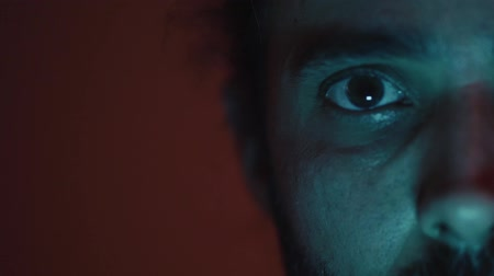 Close up portrait of the look of a man illuminated by colored lights in the dark Stok Video