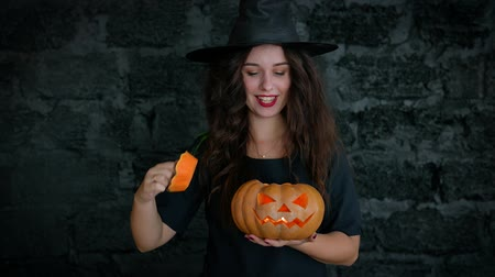 assombro : Halloween. Cute girl shows a cheerful witch. She is dressed in a black dress and hat. Girl holding pumpkin with a burning candle.
