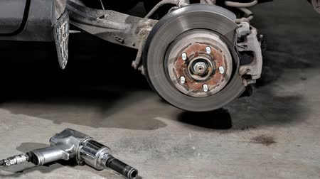 azbest : Closeup disc brake of the vehicle for repair. shot wheel, the tool for loosening the nuts. internal screw