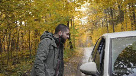 beira da estrada : Young man hitchhiker with standing on a highway in autumn. Adventure and tourism concept