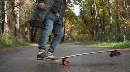 урод : Man riding on a longboard skate on a road through a forest