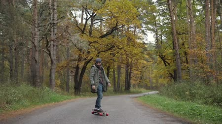bruslař : Man riding on a longboard skate on a road through a forest