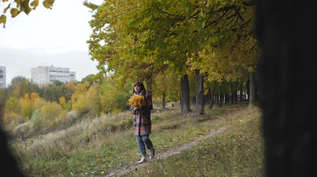 memorando : Wonderful autumnal view. Charming young happy smiling woman sitting on the grass in a park, take notes in notebook.