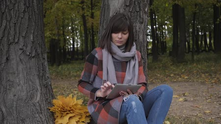 prozkoumat : Wonderful autumnal view. Charming young think woman sitting on the grass in a park, use tablet Dostupné videozáznamy