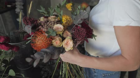 arranging : Female hands making beautiful flower composition in floral shop Stock Footage