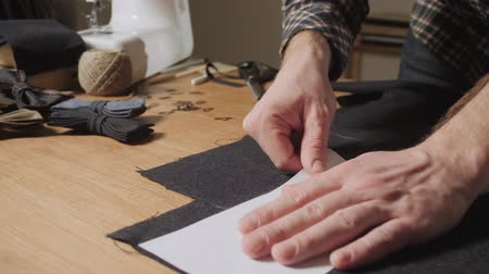 oak : Cutting wool fabric. the line pattern. Bow ties of woolen fabric. Young man working as a tailor and using a sewing machine in a textile studio. Stock Footage