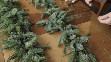 florista : Florist at work: woman hands making christmas decorations garland of fir Nobilis. Happy new year dinner feast