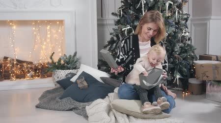 Happy mother and daughter embracing. White fireplace and decorated tree on background. Christmas or New year celebration. Стоковые видеозаписи