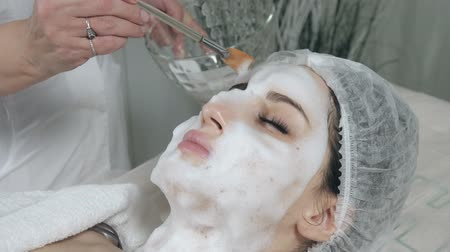 Young pretty woman receiving treatments in beauty salons. Young beautiful dark-haired woman in the office beautician lying on the couch. Facial cleansing foam using. Стоковые видеозаписи