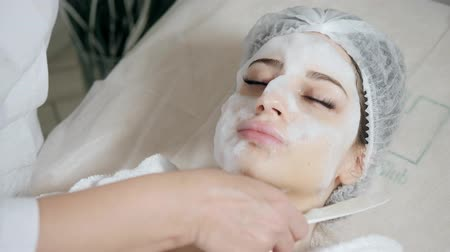 soyulması : Young pretty woman receiving treatments in beauty salons. Young beautiful dark-haired woman in the office beautician lying on the couch. Facial cleansing foam using. Stok Video