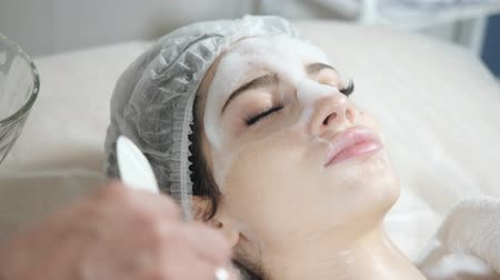 Remove with spatula foam from the face. Young pretty woman receiving treatments in beauty salons. Facial cleansing foam using.