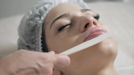 cosmetic surgery : Remove with spatula foam from the face. Young pretty woman receiving treatments in beauty salons. Facial cleansing foam using.
