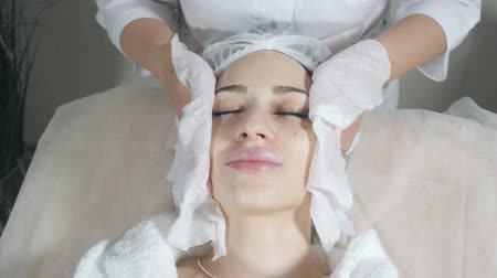 Wipe with sterile napkin face. Young pretty woman receiving treatments in beauty salons. Facial cleansing foam using.