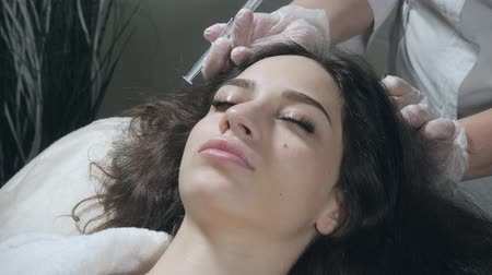 Handsome woman receives an injection in the head. The procedure makes doctor in white gloves. The concept of mesotherapy. Thrust to strengthen the hair and their growth