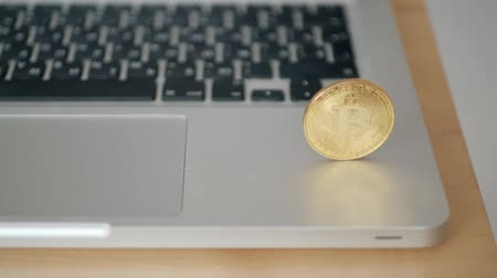 coin bitcoin falls to the keyboard on the laptop. the concept of trading cryptocurrency. The rapid growth of the currency. spinning in slow motion 180