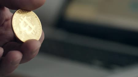 поставщик : not neat hands and a bad manicure. Man holding golden bitcoin. On the background blurred laptop. the concept of cryptocurrency.