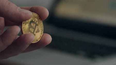 not neat hands and a bad manicure. Man holding golden bitcoin. On the background blurred laptop. the concept of cryptocurrency.