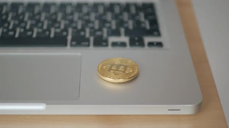 монета : coin bitcoin falls to the keyboard on the laptop. the concept of trading cryptocurrency. The rapid growth of the currency. spinning in slow motion 180