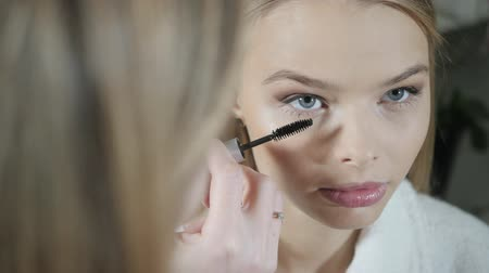 Paint eyes mascara. Makeup artist creating beautiful makeup for blondes model. Beauty and Spa centre concept Стоковые видеозаписи