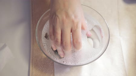 procedure moisturizing nail, hand lay in the bath with water. Close-up. Manicure beauty salon. manicurist makes the procedure for the care of nails Стоковые видеозаписи