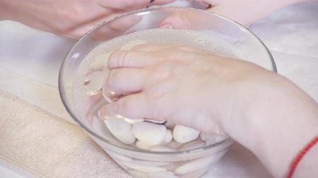 employed : procedure moisturizing nail, hand lay in the bath with water. Close-up. Manicure beauty salon. manicurist makes the procedure for the care of nails Stock Footage