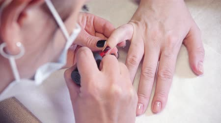 Manicure. Master applies varnish drawing on nails gel in spa . Closeup finger nail care by specialist in beauty salon.