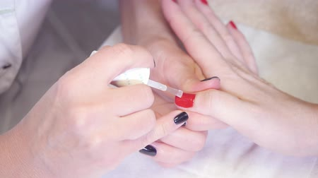 Manicure. Taking a dip from manicure bottle on foreground. Master applies varnish drawing on nails gel in spa . Closeup finger nail care by specialist in beauty salon. Стоковые видеозаписи