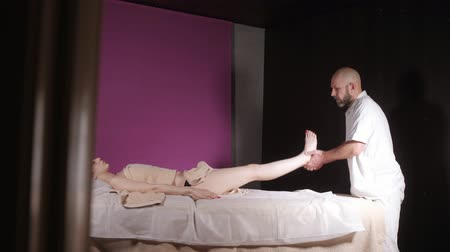 physiotherapy : Wellness foot massage. Close up of osteopath doing manipulative massage. Man hands massaging female. Spa centre concept Stock Footage