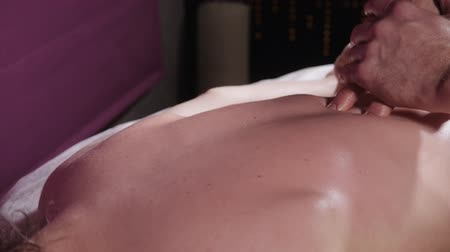 professional wellness : close-up masseur hands. Massage spine and neck, relaxed patient enjoys. low key. Man hands massaging female. Spa centre concept