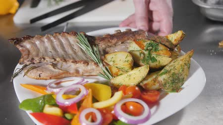 körítés : the chef prepares in the restaurant. Grilled rack of lamb with fried potatoes and fresh vegetables Stock mozgókép