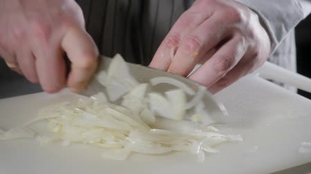 preparing : Closeup of hand with knife cutting fresh vegetable. Young chef cutting onion on a white cutting board closeup. Cooking in a restaurant kitchen
