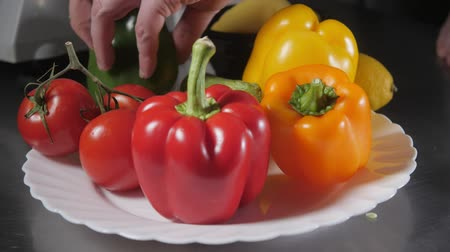 veggie : Closeup of hand with knife cutting fresh vegetable. Young chef cutting paprika on a white cutting board closeup. Cooking in a restaurant kitchen Stock Footage