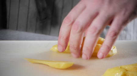 white onion : Closeup of hand with knife cutting fresh vegetable. Young chef cutting potatoes on a white cutting board closeup. Cooking in a restaurant kitchen Stock Footage