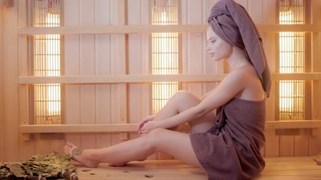 infrared : Young woman relaxing in a sauna dressed in a towel. Interior of new Finnish sauna, infrared panels for medical procedures, classic wooden sauna.